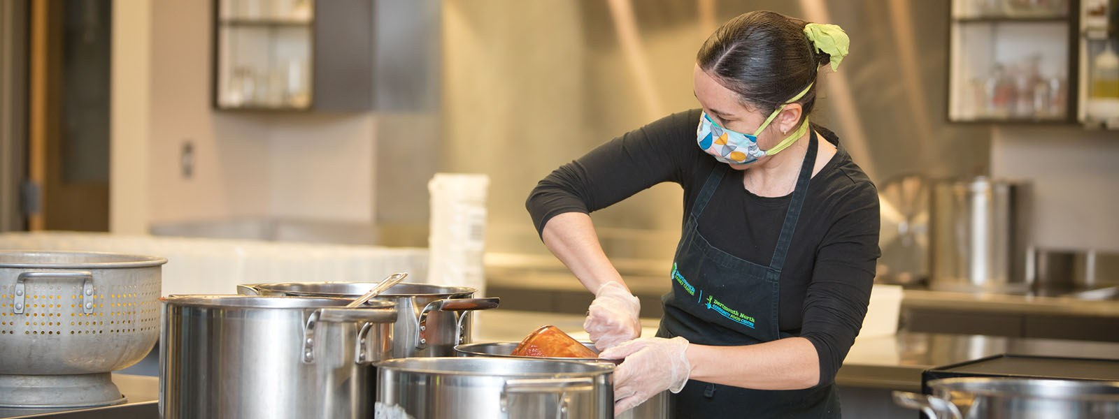 Image of female volunteer preparing food at the North Grove Community Centre.